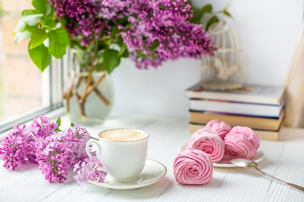 Boeket van seringen, kopje koffie, zelfgemaakte marshmallow. romantische lentemorgen