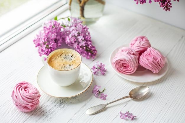 Boeket van seringen, kopje koffie, zelfgemaakte marshmallow. romantische lentemorgen.
