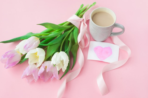 Boeket van tulpen en een koffiekopje op een roze pastel achtergrond.