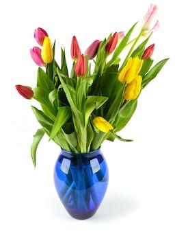 Boeket van tulpen in een blauwe glazen vaas.