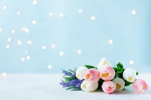 Boeket van tulpen met bokehlichten op een blauwe achtergrond.