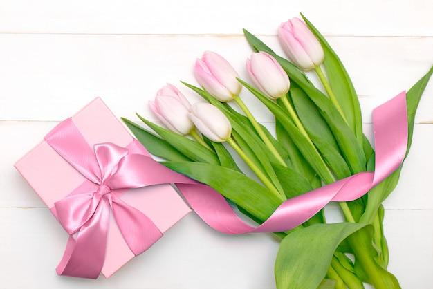 Boeket van tulpen met een cadeau op een houten witte tafel