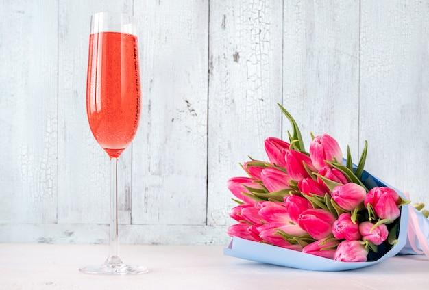 Boeket van tulpen met glas champagne op de houten achtergrond