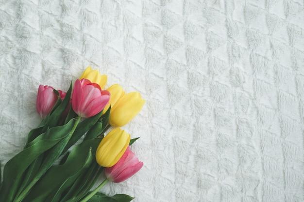 Boeket van tulpen op de rand van het bed, bovenaanzicht