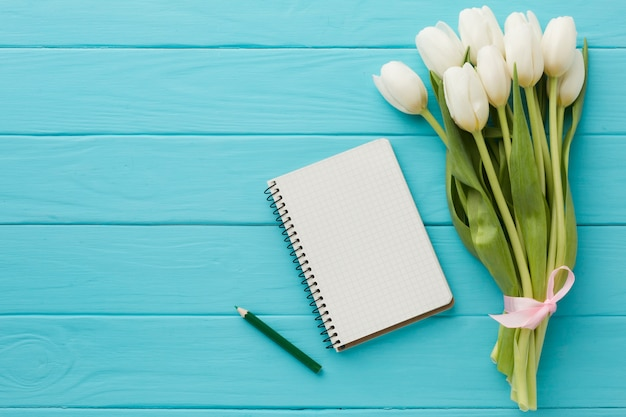 Boeket van tulpenbloemen met lege blocnote