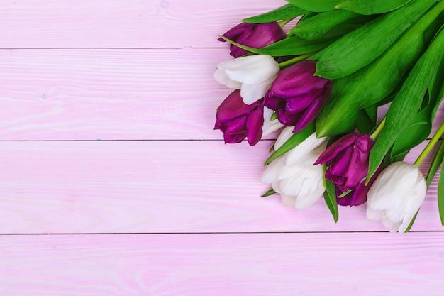 Boeket van tulpenbloemen op roze hout met copyspace