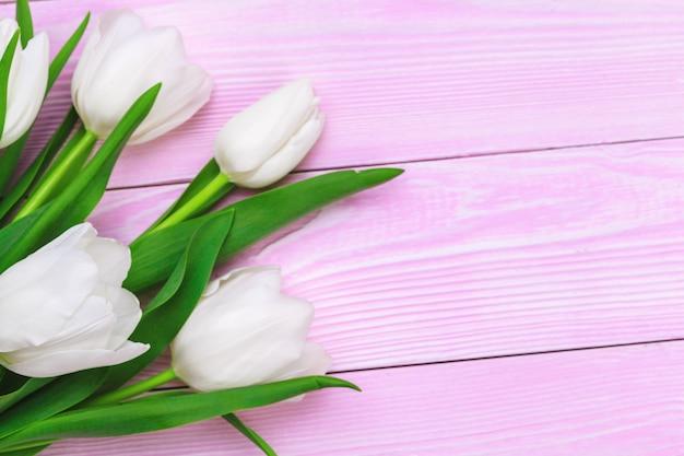 Boeket van tulpenbloemen op roze houten achtergrond met exemplaarruimte