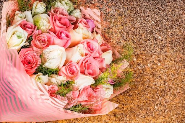 Boeket van veelkleurige rozen op een gouden achtergrond als cadeau voor valentijnsdag of bruiloft