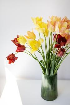 Boeket van veelkleurige tulpen in een groene vaas. verse lentebloemen, florale achtergrond. vakantieconcept.