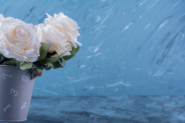 Boeket van vele witte rozen geplaatst op blauw.