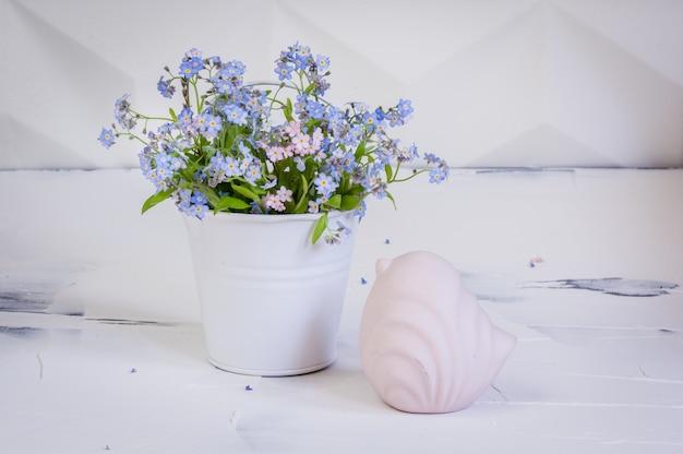 Boeket van vergeet-mij-nietjes in metalen emmer en een roze vogeltje op witte achtergrond