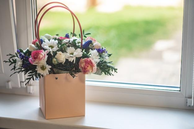 Boeket van verschillende bloemen in papieren zak met handvatten, staand op een vensterbank