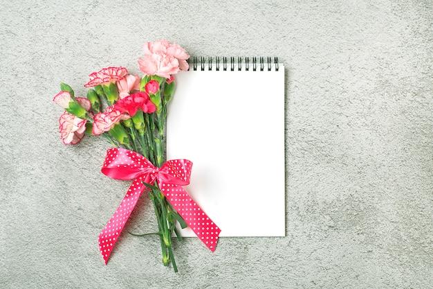 Boeket van verschillende roze anjer bloemen, witte notebook, pen op grijze betonnen tafel