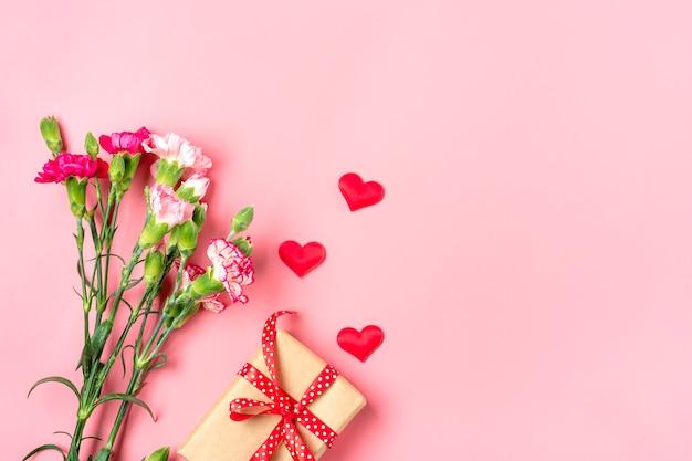Boeket van verschillende roze anjerbloemen, geschenkdoos, harten op roze achtergrond