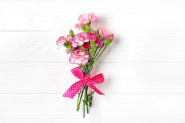 Boeket van verschillende roze anjerbloemen op witte houten achtergrond