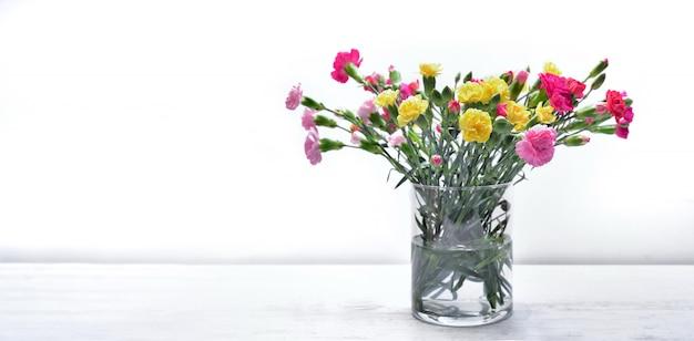 Boeket van verse bloemen anjer kleurrijk in een glazen pot op een tafel