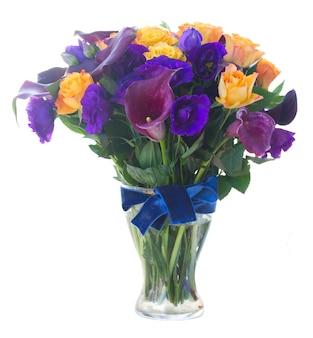 Boeket van verse calla lelie, rozen en eustoma bloemen in glazen vaas op wit wordt geïsoleerd