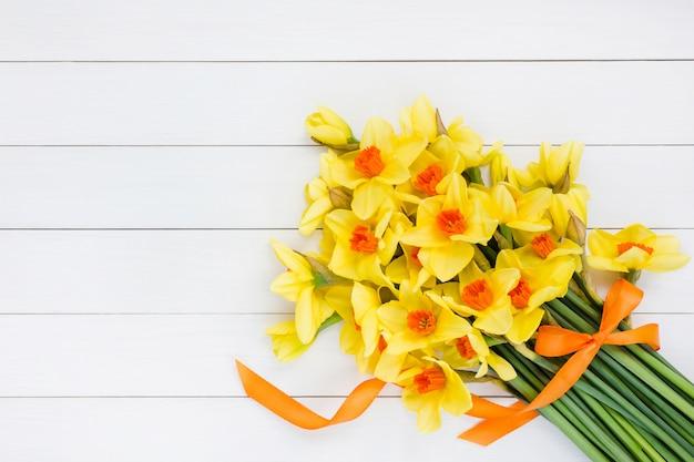 Boeket van verse lente narcissus versierd met lint op witte houten tafel.