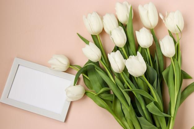 Boeket van verse lente witte tulpen ligt op een lichte pastel achtergrond, bovenaanzicht