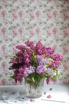 Boeket van violet lila in een vaas. stilleven met bloeiende takken van sering in vazen. wenskaart mock-up. ruimte voor tekst.