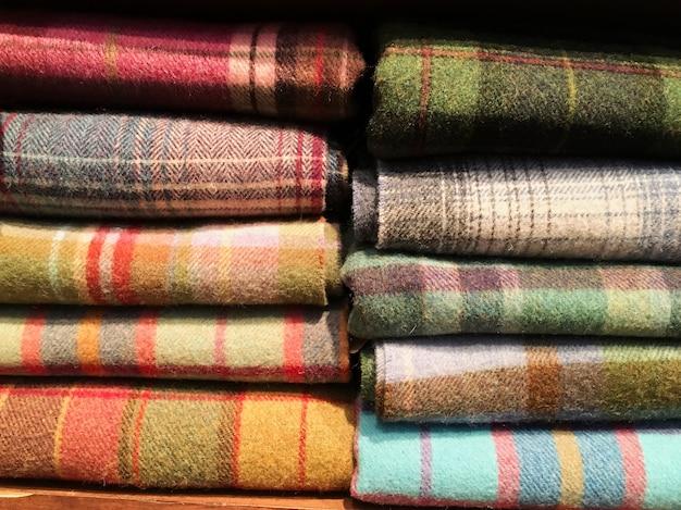 Boeket van warme gebreide pastelkleuren van diverse stoffenpatronen in een stapel op wit.