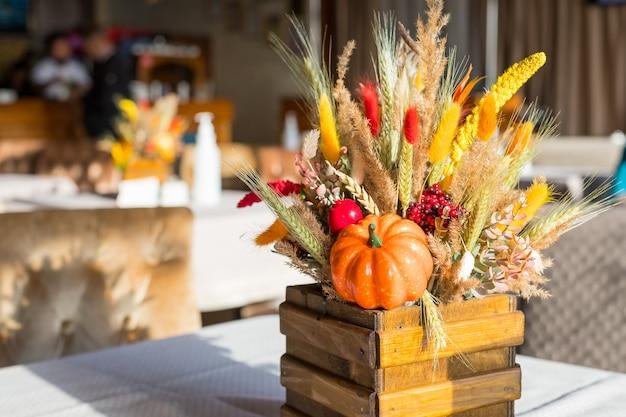 Boeket van wilde bloemen in het restaurant. herfst compositie in een houten vaas. herfst interieur. oranje pompoen met rode bessen, droge herfstbloemen en gele bladeren. oogst, gezellige, feestelijke sfeer.