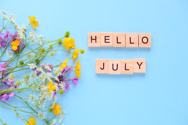 Boeket van wilde bloemen op blauwe muur hallo juli. inscriptie gemaakt van houten kubussen