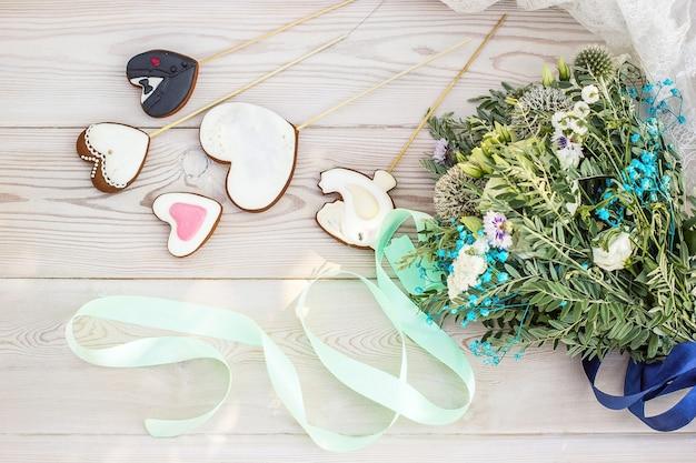 Boeket van wilde bloemen witte houten ondergrond en hartvormige gemberkoekjes op stokjes