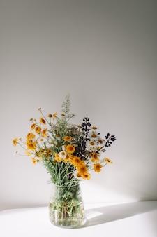 Boeket van wilde natuurlijke bloemen in een vaas op tafel