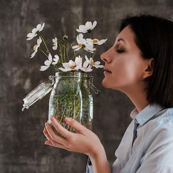 Boeket van witte bloemen in een glazen vaas in handen van een vrouw