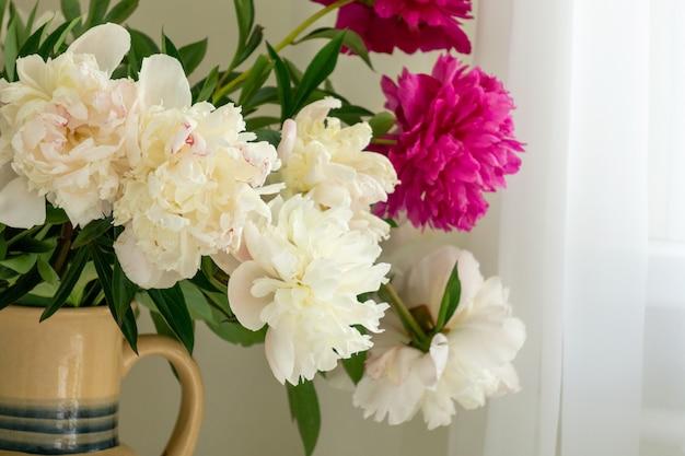 Boeket van witte en roze pioenrozen in kruik op lichte achtergrond