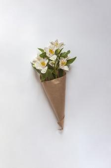 Boeket van witte peruaanse lelies omwikkeld met bruin papier op een witte achtergrond