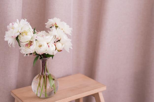 Boeket van witte pioenrozen in een glazen vaas op tafel
