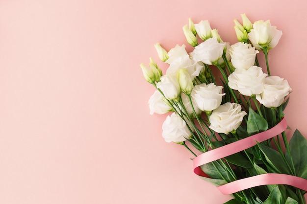 Boeket van witte rozen met roze lint