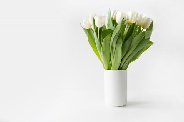 Boeket van witte tulp in vaas op wit.