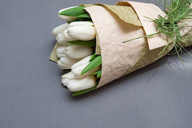 Boeket van witte tulpen op een grijze tafel. flay lat.