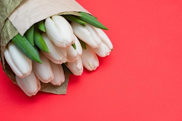 Boeket van witte tulpen op een rode tafel. plat leggen.