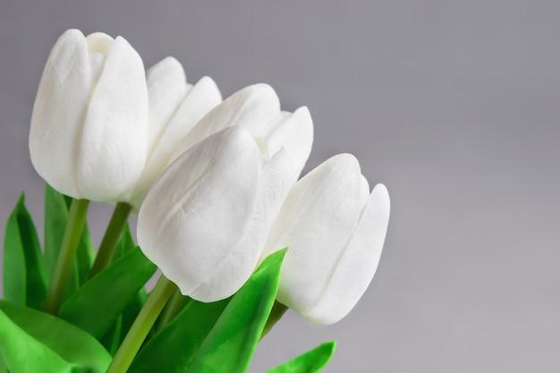 Boeket van witte tulpen op grijze achtergrond, cadeau voor vrouw, concept van vrouwenvakantie