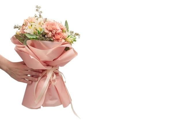 Boeket van zacht roze bloemen in roze inpakpapier in handen van de vrouw geïsoleerd op wit.