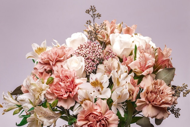 Boeket van zachtroze bloemen in roze cadeaupapier.