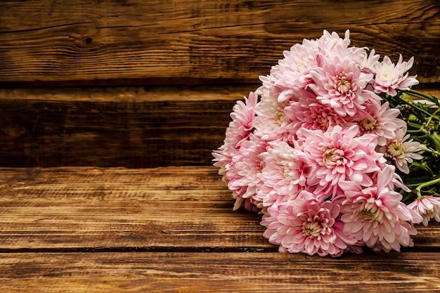 Boeket van zachtroze chrysanten. mooi cadeau op vintage houten achtergrond