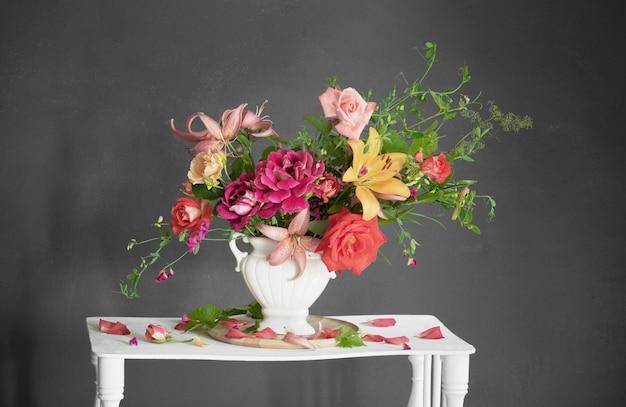 Boeket van zomerbloemen in vaas op vintage witte houten plank op donkere ondergrond