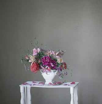 Boeket van zomerbloemen in vaas op vintage witte houten plank