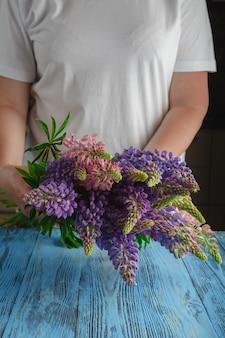 Boeket van zomerbloemen in vrouwelijke handen tegen een houten oppervlak