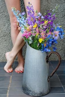 Boeket veelkleurige wilde bloemen in een oude metalen kan