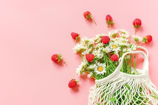 Boeket veldmadeliefjes in herbruikbare eco-boodschappentas en aardbeien