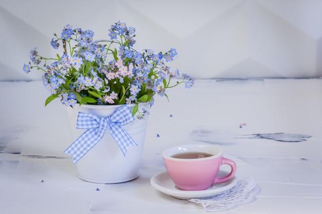 Boeket vergeet-mij-nietjes in metalen emmer en en kopje thee op witte achtergrond.