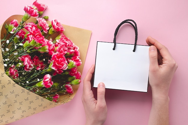 Boeket verse anjers en een papieren witte geschenk tas op roze achtergrond
