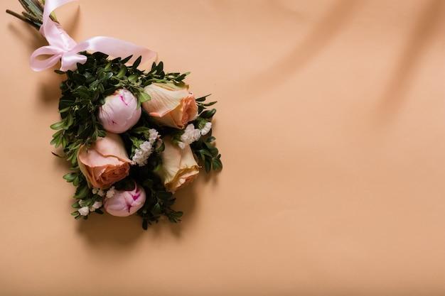 Boeket verse bloemen op een beige achtergrond met ruimte voor tekst. bruidsboeket