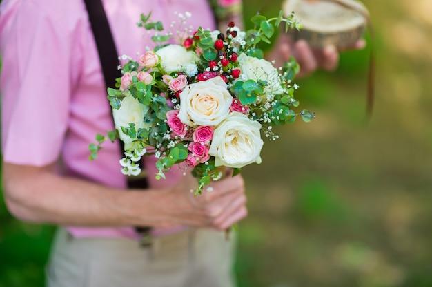 Boeket verse bloemen van de bruid in de handen van de bruidegom